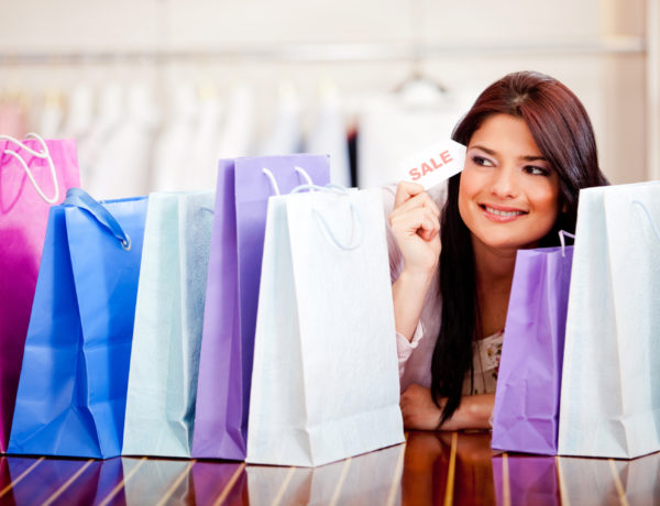 Beautiful woman with shopping bags holding a sale tag