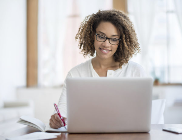 Young black woman working at home on a laptop computer and wearing glasses while looking very happy